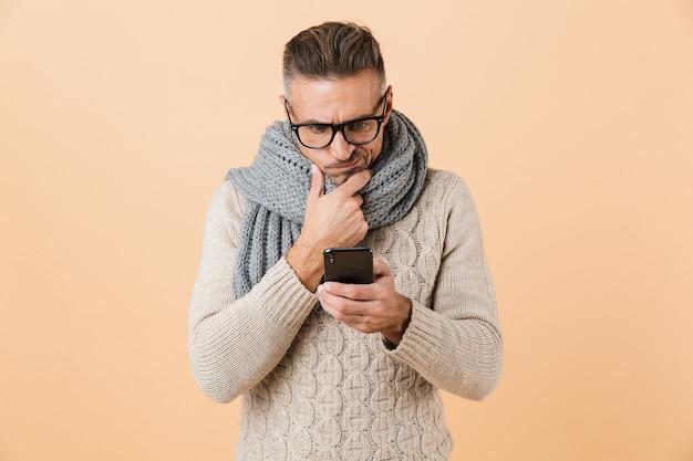 Ritratto di un uomo pensieroso vestito in maglione e sciarpa in piedi isolato sopra il muro beige, utilizzando il telefono cellulare