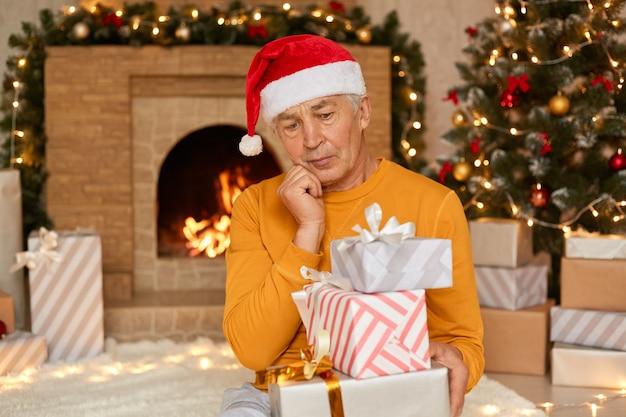 Ritratto di pensieroso uomo anziano in cappello di babbo natale, tenere i pacchetti che porta per qualcuno