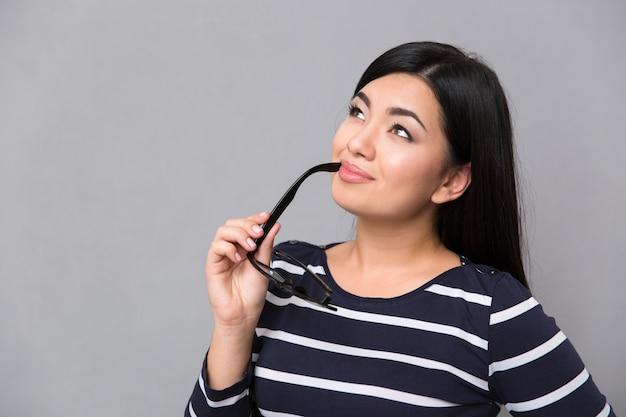 Ritratto di una donna pensierosa tenendo gli occhiali e guardando il copyspace sopra il muro grigio