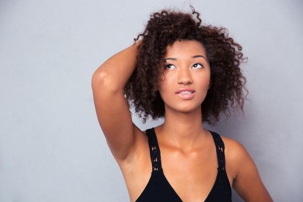 Ritratto di una donna pensierosa in piedi sul muro grigio e guardando il copyspace