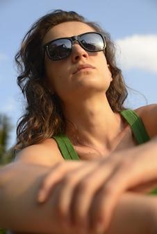 Ritratto di una donna pensierosa in occhiali da sole. lei è in spiaggia