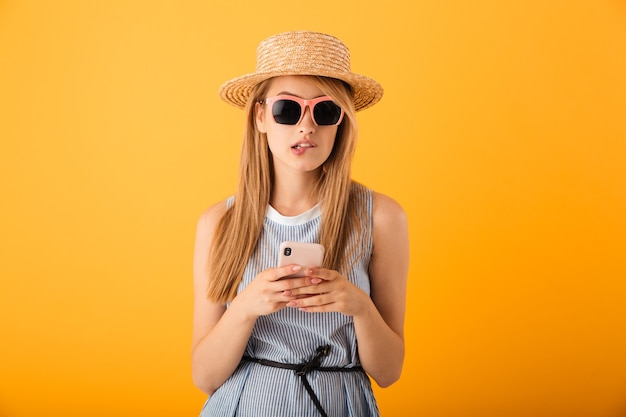 Ritratto di una giovane donna bionda pensierosa in cappello estivo