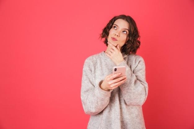 Ritratto di una giovane donna pensierosa in piedi isolato su rosa, parlando al telefono cellulare
