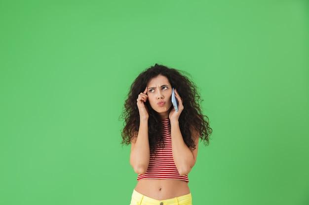 Ritratto di una donna perplessa 20s vestita in modo casual mentre parla al telefono cellulare isolato su verde