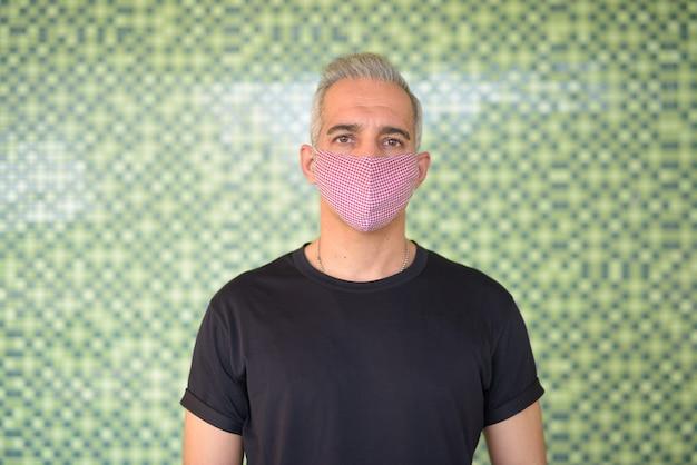 Ritratto di uomo persiano con maschera per la protezione dallo scoppio del virus corona e dall'inquinamento contro la parete verde all'esterno