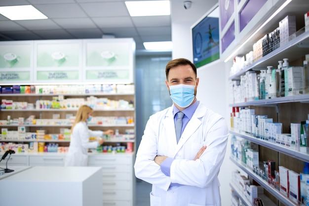 Ritratto del farmacista che indossa la maschera per il viso e camice bianco in piedi nel negozio di farmacia durante la pandemia del virus corona.