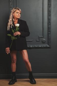 Foto ritratto carino di mezza età 45 anni donna bionda in camera domestica con rose. donna in vestiti di stile in background interni. servizio di incontri di concetto. al chiuso, donna matura sicura di sé