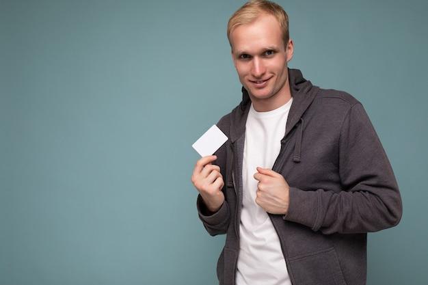 Foto del ritratto dell'uomo biondo felice bello che porta maglione grigio e maglietta bianca