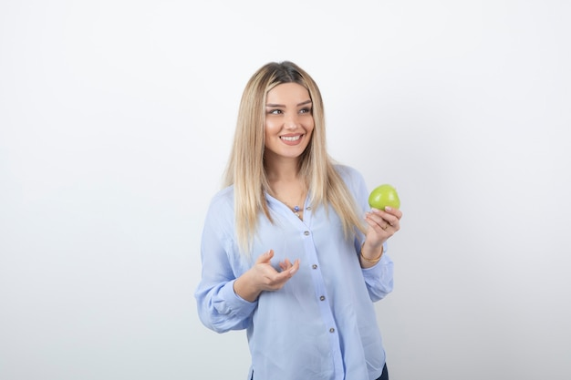 Foto ritratto di un modello di donna piuttosto attraente in piedi e in possesso di una mela fresca verde.