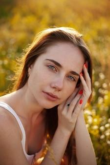 Foto ritratto di una donna al tramonto foto estiva di una donna in un campo con fiori di campo tempo d'oro foto del primo piano mani vicino al viso donna con le lentiggini