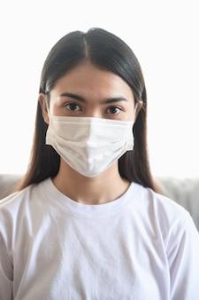 Foto del ritratto di giovane donna asiatica che indossa la maschera chirurgica in casa per proteggere il coronavirus (covid-19) durante la crisi di pandemia di epidemia di virus in tutto il mondo. Foto Premium