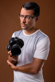 Ritratto dell'uomo del fotografo che pensa sul marrone