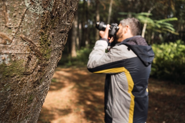 Ritratto di un fotografo che fotografa in un parco.