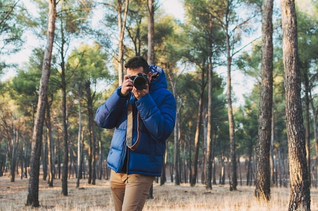 Ritratto di un fotografo che scatta una foto con la sua fotocamera reflex nella foresta