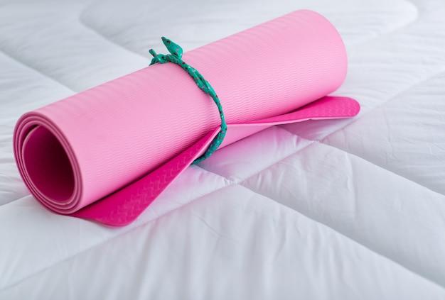 Ritratto di tappetino yoga rosa e corda verde legata su una coperta bianca in camera da letto con spazio per le copie. concetto di sfondo sportivo.