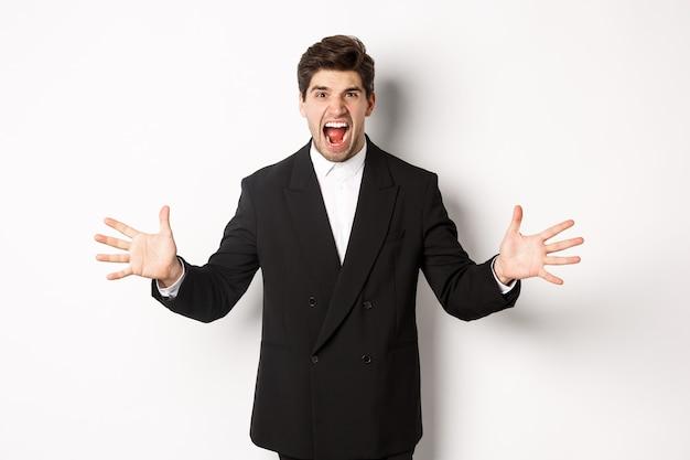 Ritratto di uomo d'affari incazzato e frustrato in tuta, gridando arrabbiato e stringendo la mano, in piedi angosciato su sfondo bianco
