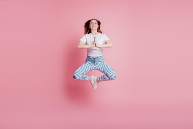 Il ritratto della ragazza pazza giocosa che salta nell'aria medita la posa del loto su fondo rosa