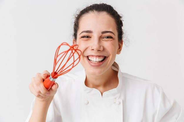 Ritratto di una giovane donna allegra con utensili da cucina