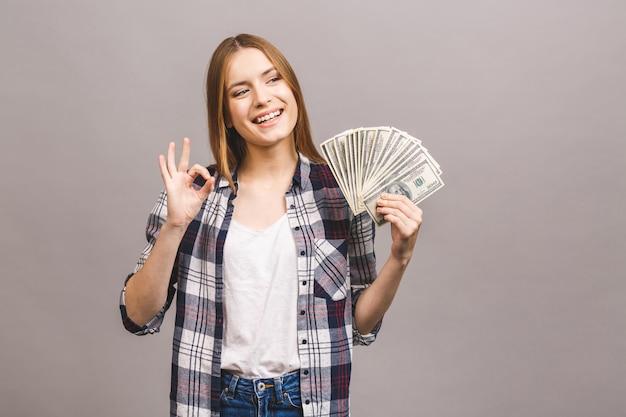 Ritratto di una giovane donna allegra con capelli lunghi che tengono mazzo di banconote dei soldi e che esaminano macchina fotografica. segno ok.