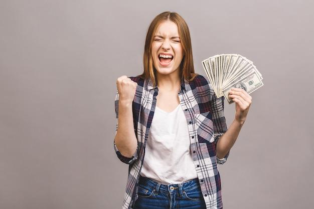 Ritratto di una giovane donna allegra con capelli lunghi che tengono mazzo di banconote dei soldi e che esaminano macchina fotografica