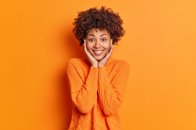 Ritratto di donna dall'aspetto piacevole tiene le mani sul viso ammira qualcosa sorride delicatamente e guarda direttamente la telecamera indossa un maglione isolato sopra il muro arancione vivido