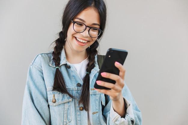 Ritratto di una bella ragazza carina e contenta in giacca di jeans che indossa occhiali isolati sul muro grigio usando il telefono cellulare.
