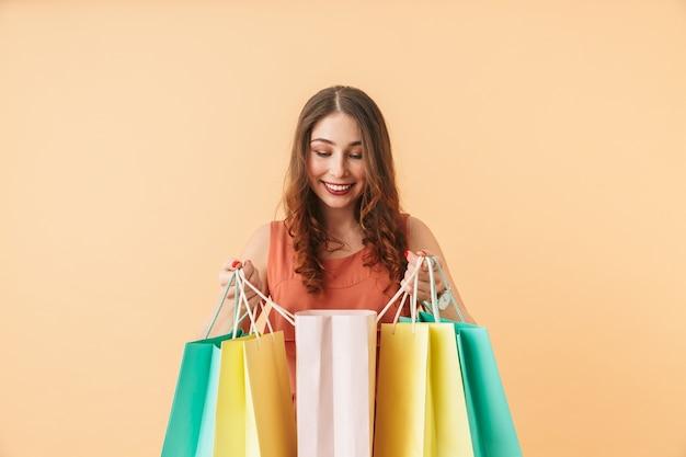 Ritratto di ragazza soddisfatta 20s che trasportano sacchetti della spesa di carta colorata, mentre in piedi isolato