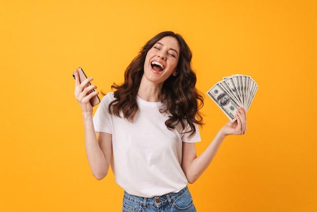 Ritratto di una giovane donna di grido emotiva felice soddisfatta che posa isolata sopra la parete gialla facendo uso del denaro della tenuta del telefono cellulare.