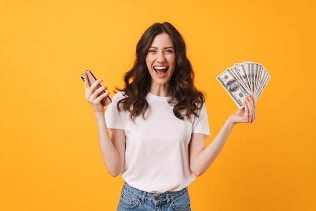Ritratto della giovane donna di grido felice felice che posa isolata sopra la parete gialla facendo uso dei soldi della tenuta del telefono cellulare.