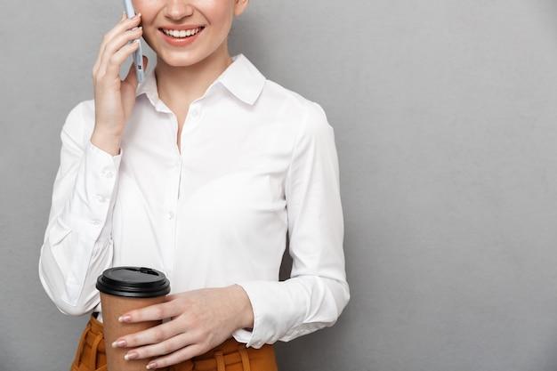 Ritratto di felice imprenditrice rossa 20s in abbigliamento formale utilizza lo smartphone in ufficio e beve caffè da asporto dal bicchiere di plastica isolato su grigio