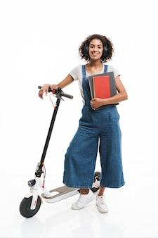 Ritratto di donna contenta che usa le cuffie e tiene quaderni mentre si guida su uno scooter isolato su un muro bianco