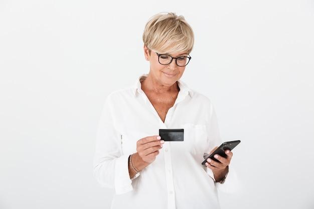 Ritratto di donna adulta positiva con capelli biondi corti che tiene cellulare e carta di credito isolate su muro bianco in studio