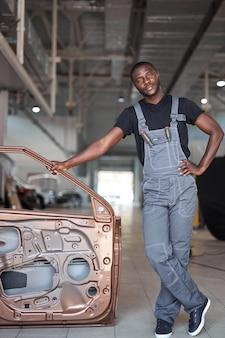 Ritratto del meccanico automatico afroamericano positivo in uniforme che posa dopo il lavoro