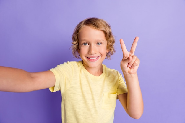Il ritratto del ragazzo positivo prende la foto del selfie fa in modo che il v-sign indossa la maglietta gialla isolata sopra il fondo di colore viola