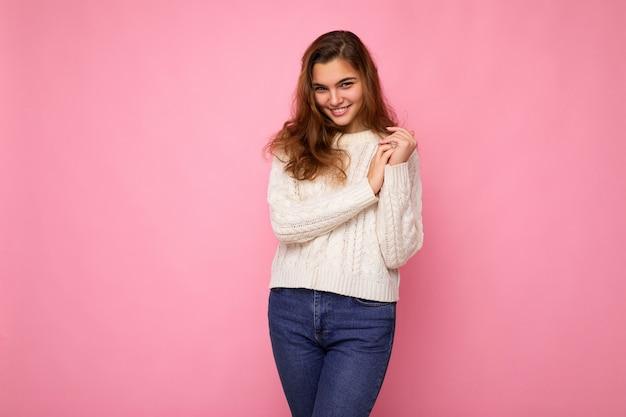 Ritratto di donna alla moda allegra positiva in abbigliamento formale che guarda l'obbiettivo isolato sulla superficie rosa con lo spazio della copia