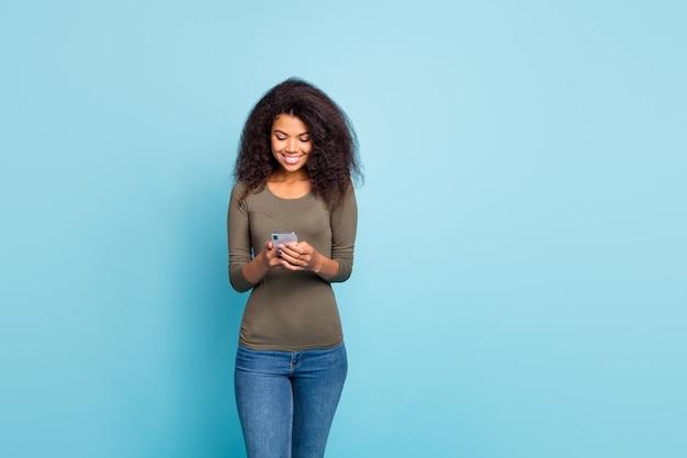 Ritratto di ragazza mulatta blogger concentrato allegro positivo utilizzando il suo smartphone leggere feedback tipo feednews sui blog indossare jeans denim maglione verde isolato su parete di colore blu