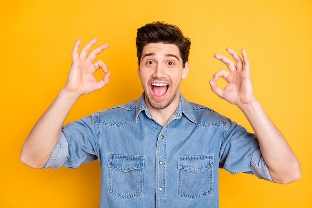Il ritratto del promotore di ragazzo funky allegro positivo mostra il segno giusto seleziona gli annunci suggeriscono la promozione che indossa un vestito elegante isolato sopra la parete di colore giallo