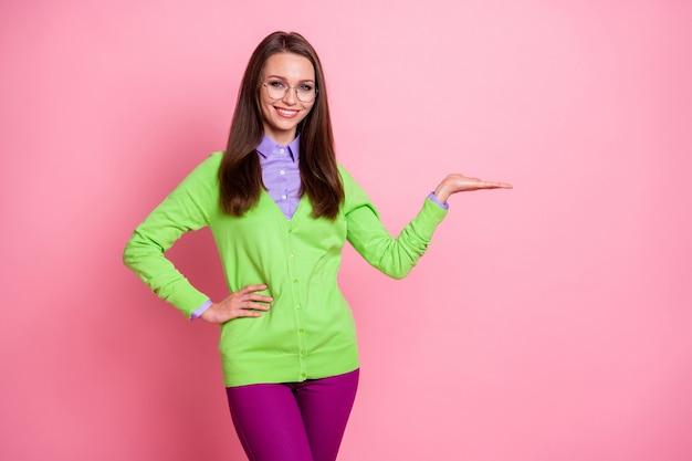 Il ritratto della ragazza allegra positiva tiene il copyspace della mano indossa pantaloni isolati sullo sfondo di colore pastello