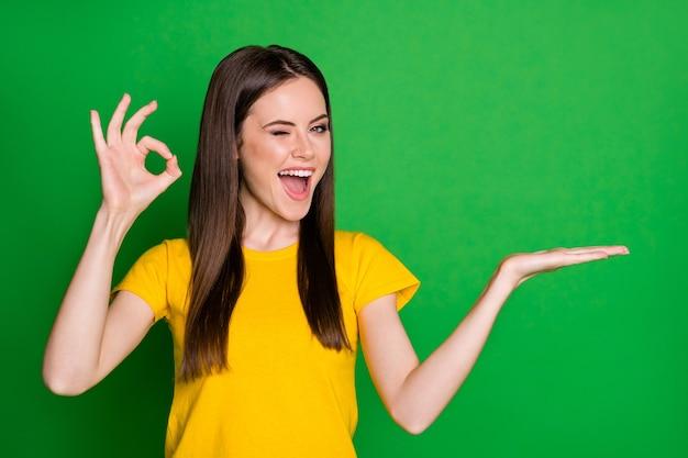 Il ritratto del promotore positivo della ragazza allegra tiene la promozione presente degli annunci della mano