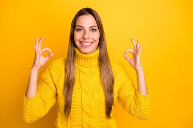 Il ritratto del promotore positivo della ragazza allegra mostra il segno giusto consiglia l'annuncio pubblicizza la promozione indossa il ponticello vivido isolato sopra la parete di colore giallo