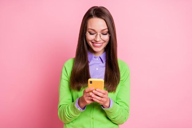 Il ritratto della ragazza allegra positiva usa il fondo di colore pastello isolato delle notizie del social network del cellulare