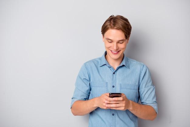 Il ritratto del ragazzo allegro positivo utilizza lo smartphone per leggere le notizie sui social media e godersi l'abbigliamento elegante isolato su sfondo di colore grigio