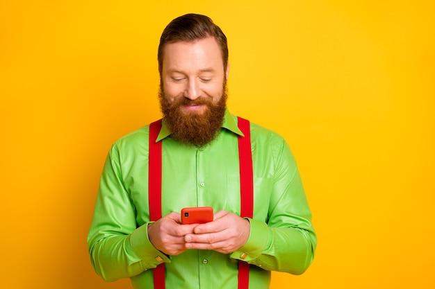 Il ritratto della persona positiva blogger irlandese allegra utilizza lo smartphone leggere le notizie sui social media ripubblicare condividere indossare bretelle isolate su un colore brillante