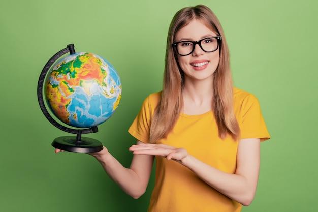 Il ritratto di una signora allegra positiva dimostra il sorriso raggiante del globo che indossa occhiali da vista t-shirt gialla