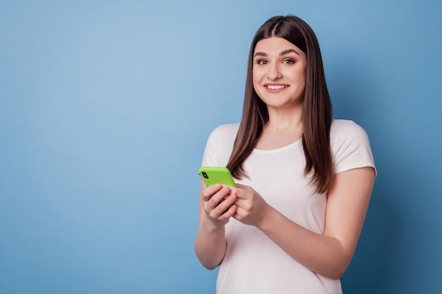 Ritratto di una signora allegra positiva che tiene il telefono con un sorriso bianco lucido della fotocamera su sfondo blu