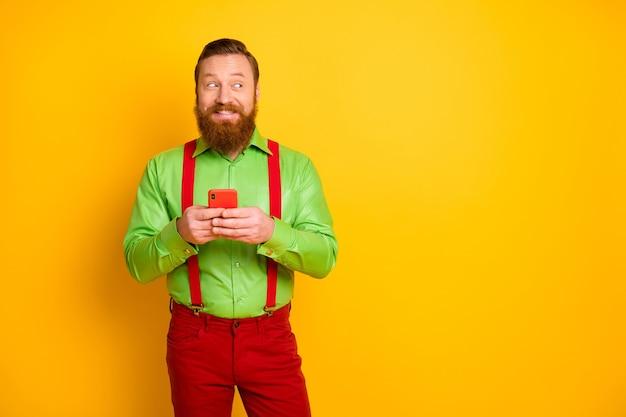 Ritratto positivo uomo allegro utilizzare smartphone multimedia guardare copyspace condividere ripubblicare social network notizie indossare bretelle pantaloni pantaloni isolati colore brillante