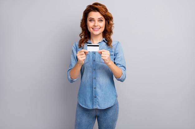 Il ritratto della carta di credito della stretta della donna allegra positiva consiglia di pagare l'acquisto con il sistema di servizio di pagamento del credito indossare vestiti di bell'aspetto isolati sopra la parete di colore grigio