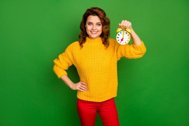 Ritratto di donna allegra positiva tenere l'orologio con il maglione di usura di tempo di mattina presto isolato sopra la parete di colore di lucentezza