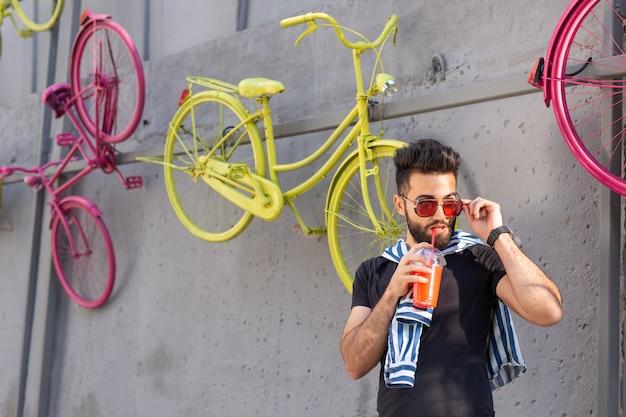 Ritratto di un giovane arabo allegro positivo con un bicchiere di succo con una cannuccia mentre si cammina in città in una calda giornata estiva di sole. il concetto di riposo dopo lo studio e il lavoro nei fine settimana.