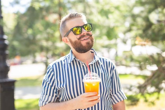 Ritratto di un giovane allegro positivo con un bicchiere di succo con una cannuccia mentre si cammina nel parco in una calda giornata estiva di sole. il concetto di riposo dopo lo studio e il lavoro nei fine settimana.